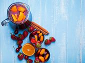 stock photo of sangria  - Sangria with cherries and strawberries on the blue wooden background - JPG