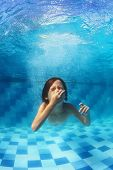 pic of amusement  - Amusing face portrait of boy swimming underwater and diving with fun in blue pool  - JPG