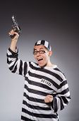 stock photo of prison uniform  - Funny prisoner with firearm isolated on gray - JPG