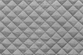 stock photo of quilt  - silvery quilted synthetic fabric with grained texture for empty and pure abstract backgrounds - JPG