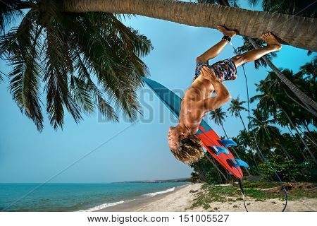 Young man with surfboard on coconut palm on beach