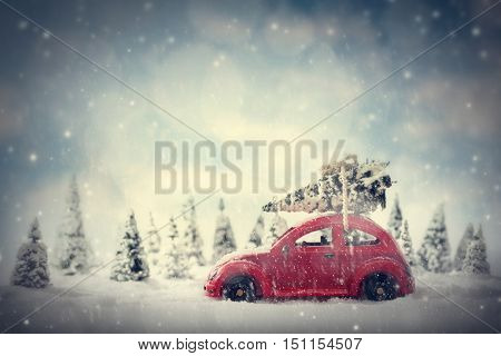 Retro toy car carrying tiny Christmas tree. Fairytale, miniature scenery with snow and forest. Gener