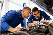 auto service, repair, maintenance and people concept - mechanic men with wrench repairing car at wor poster