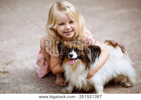 poster of Happy Little Girl With A Dog Standing On The Road In The Park. Cute Little Girl Hugging A Dog, Smili