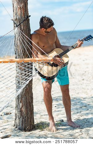 Young Shirtless Man Playing Acoustic