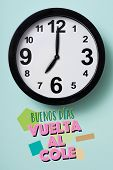 closeup of a clock and the text good morning, back to school written in spanish on a green backgroun poster