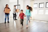 Excited Family Carrying Boxes Into New Home On Moving Day poster