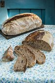 Whole Rye And Whole Wheat Sourdough Bread  On A Flowered Table Cloth poster