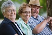 stock photo of senior-citizen  - Portrait of senior friends sitting together in park - JPG