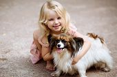 Happy Little Girl With A Dog Standing On The Road In The Park. Cute Little Girl Hugging A Dog, Smili poster
