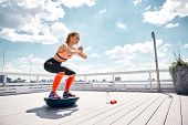 Athlete Girl Is Enjoying Work Out With Outfit On High Balcony. She Is Doing Squats On Bosu Platform  poster