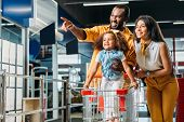 Smiling African American Man Pointing By Finger To Little Daughter And Wife In Supermarket poster