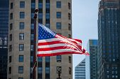 Close Up Of Waving Flag Of The United States In Downtown Chicago With High Buildings In The Backgrou poster