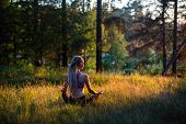 Yoga woman meditates in a clearing in the woods. Peaceful and harmony.  poster