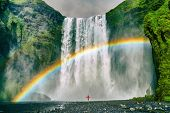 Iceland waterfall travel nature famous tourist destination. Skogafoss waterfall with rainbow and wom poster