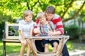 Two Funny Handsome Kid Boys And Young Father Playing Together Checkers Game. Sons, Siblings Children poster