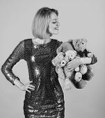 Girl With Smiling Curious Face Plays With Beige Soft Toys. Lady With Blond Hair Hugs Cute Toy Bears. poster