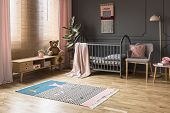 Real Photo Of A Baby Crib Standing Between A Low Cupboard And An Armchair, Lamp And Stool In Childs poster