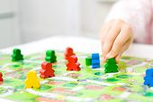 Green People Figure In Hand Of Child. Red, Blue, Green Wood Chips In Children Play - Board Game And  poster