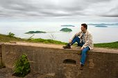 stock photo of stockade  - a lonely man resting on the wall of fortress on Russian Island - JPG