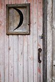 stock photo of outhouse  - Closeup of weathered old wooden outhouse door with crescent moon window faded pink peeling paint and rusted handle - JPG