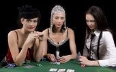 image of moulin rouge  - Three attractive girls dressed in moulin rouge clothing playing cards at green poker table - JPG
