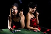 stock photo of moulin rouge  - Two attractive woman playing poker and smoking cigarettes at the poker table - JPG