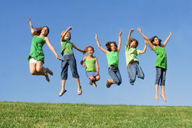 picture of children playing  - happy healthy smiling group of kids children jumping for joy at summer camp - JPG