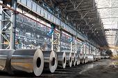 picture of construction machine  - Long row of rolls of aluminum in production shop of plant - JPG