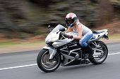 stock photo of crotch-rocket  - Abstract blur of a pretty girl driving a motorcycle at highway speeds - JPG