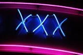 stock photo of pornography  - XXX neon sign advertising an adult licensed sex shop in a red light district - JPG