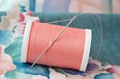 Threaded needle in spool of peach colored polyester thread with swatches of fabric.  Macro with shal