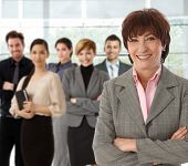stock photo of work crew  - Portrait of happy senior businesswoman and her business team - JPG