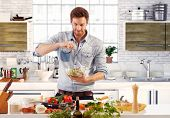image of handsome-male  - Handsome man cooking at home preparing salad in kitchen - JPG