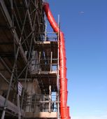 foto of chute  - A red plastic rubbish chute and scaffolded building against blue sky - JPG