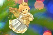 Постер, плакат: christmas decoration figure of little angel playing the harp against bokeh background
