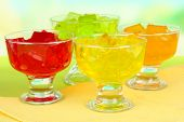 Tasty jelly cubes in bowls on table on light background