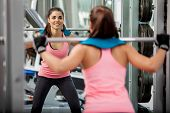 pic of squatting  - Beautiful young woman doing some squats with a barbell and smiling at the gym - JPG