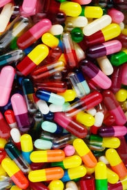 image of pyrex  - Empty medicinal capsules in varying colors sizes and styles inside a glass container - JPG