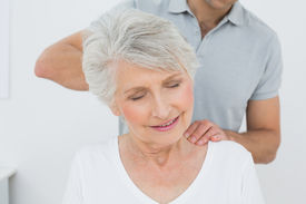 image of medical condition  - Male physiotherapist massaging a senior woman - JPG