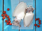 stock photo of devilfish  - raw cuttlefish and chery tomatoes  on the blue board - JPG