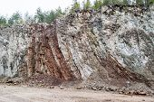 stock photo of meteorite  - Old limestone quarry with vertical layered sedimentation - JPG