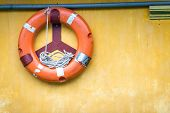 picture of nautical equipment  - Yellow wall with orange buoy on it - JPG