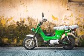 picture of stonewalled  - Green scooter against old house - JPG
