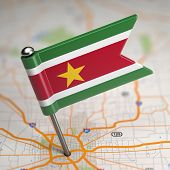 image of suriname  - Small Flag Republic of Suriname on a Map Background with Selective Focus - JPG