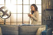 picture of sms  - Young woman writing sms in loft apartment  - JPG