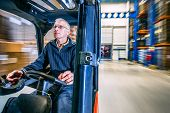 pic of forklift driver  - man driving a forklift through a warehouse in a factory - JPG