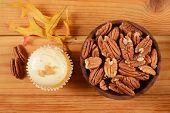 foto of pecan  - A gourmet pecan pie cupcake with a bowl of pecans - JPG