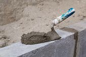 pic of trowel  - Trowel with cement on a constructed wall outdoors - JPG