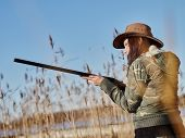 stock photo of hunt-shotgun  - Waterfowl hunting female hunter use the shotgun reeds and blue sky on background - JPG